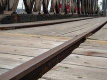 Fermez-vous de la voie ferrée rouillée dans un secteur de dock en bois photo libre de droits