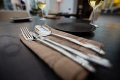 Fermez-vous de manger les ustensiles et la serviette sur la table photographie stock