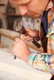 Fermez-vous de Mason At Work On Carving en pierre dans le studio Photo libre de droits