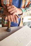 Fermez-vous de Mason At Work On Carving en pierre dans le studio Image stock