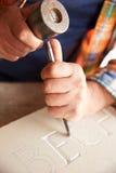 Fermez-vous de Mason At Work On Carving en pierre dans le studio Photographie stock libre de droits