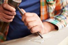 Fermez-vous de Mason At Work On Carving en pierre dans le studio Photo stock