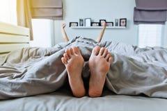 Fermez-vous de nu-pieds sous la couverture grise sur le lit Photographie stock libre de droits
