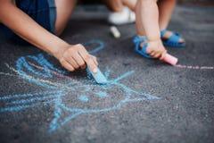 Fermez-vous de peu de dessin de fille avec des craies sur le trottoir photographie stock