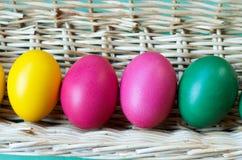 Fermez-vous de quatre oeufs de pâques colorés dans un panier Images libres de droits