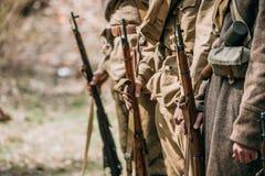 Fermez-vous de re-enactors habillé comme les soldats soviétiques d'infanterie des prises de la deuxième guerre mondiale fusille d images stock