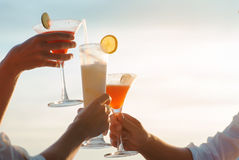 Fermez-vous de trois amis faisant tinter avec le cocktail en verre Image stock