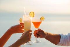 Fermez-vous de trois amis faisant tinter avec le cocktail en verre Images stock