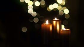 Fermez-vous de trois bougies brûlantes avec le fond brouillé de lumière de Noël Dans le cadre clignote une ombre foncée, se ferma banque de vidéos