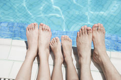 Fermez-vous de trois jambes des personnes par le côté de piscine Image stock