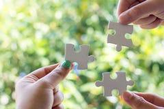 Fermez-vous de trois mains tenant le puzzle, photographie stock libre de droits