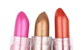 Fermez-vous de trois rouges à lèvres dans différentes couleurs d'isolement sur le petit morceau Photographie stock