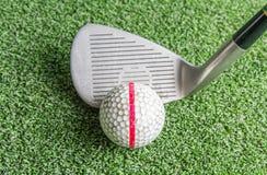 Fermez-vous, de vieux boules de golf et fer sur l'herbe artificielle Images stock