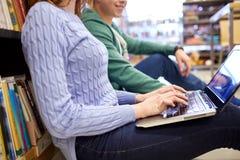 Fermez-vous des étudiants heureux avec l'ordinateur portable dans la bibliothèque Image stock
