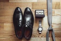 Fermez-vous des accessoires modernes de marié anneaux de mariage, cravate grise, chaussures en cuir et montre Image libre de droits