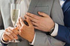 Fermez-vous des ajouter gais masculins au verre de champagne Photos stock
