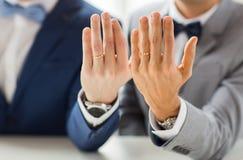 Fermez-vous des ajouter gais masculins aux anneaux de mariage dessus Photographie stock libre de droits