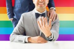 Fermez-vous des ajouter gais masculins aux anneaux de mariage dessus Photo stock