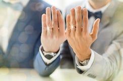 Fermez-vous des ajouter gais masculins aux anneaux de mariage dessus Images stock