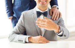 Fermez-vous des ajouter gais masculins aux anneaux de mariage dessus Photos stock