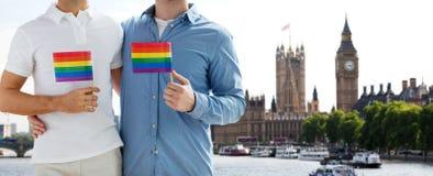 Fermez-vous des ajouter gais masculins aux drapeaux d'arc-en-ciel Images stock