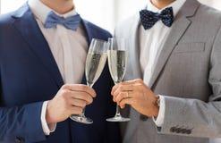Fermez-vous des ajouter gais masculins aux verres de champagne Photo stock