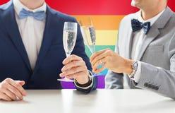 Fermez-vous des ajouter gais masculins aux verres de champagne Images stock