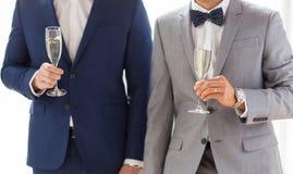 Fermez-vous des ajouter gais masculins aux verres de champagne Photographie stock libre de droits