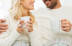 Fermez-vous des ajouter heureux aux tasses de thé à la maison Photographie stock libre de droits