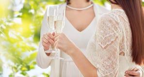 Fermez-vous des ajouter lesbiens aux verres de champagne Photographie stock libre de droits