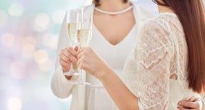 Fermez-vous des ajouter lesbiens aux verres de champagne Images stock