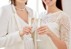 Fermez-vous des ajouter lesbiens aux verres de champagne Photos stock