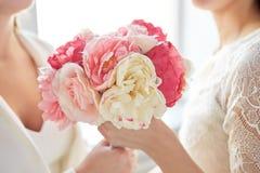 Fermez-vous des ajouter lesbiens heureux aux fleurs Photos stock