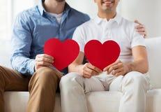 Fermez-vous des ajouter masculins gais heureux aux coeurs rouges Image stock