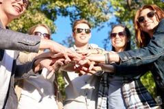 Fermez-vous des amis adolescents avec des mains sur le dessus Photos stock