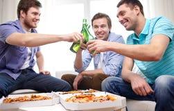 Fermez-vous des amis avec de la bière et la pizza à la maison Photos libres de droits