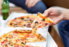 Fermez-vous des amis avec de la bière et la pizza à la maison Images stock