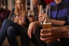 Fermez-vous des amis avec des boissons appréciant la partie de Chambre Photo stock