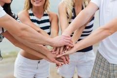 Fermez-vous des amis avec des mains sur le dessus à la plage Images libres de droits