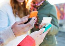 Fermez-vous des amis avec des smartphones dehors Images stock