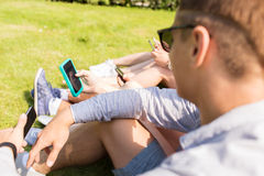 Fermez-vous des amis avec des smartphones sur l'herbe Images stock