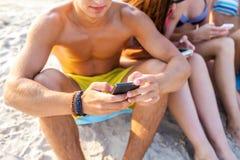 Fermez-vous des amis avec des smartphones sur la plage Photos stock
