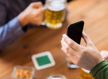 Fermez-vous des amis avec le smartphone et la bière Photographie stock libre de droits