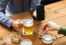 Fermez-vous des amis avec le smartphone et la bière Photo stock