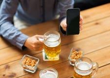 Fermez-vous des amis avec le smartphone et la bière Images stock