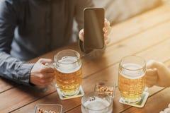 Fermez-vous des amis avec le smartphone et la bière Image stock