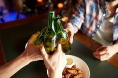 Fermez-vous des amis buvant de la bière à la barre ou au bar Photographie stock