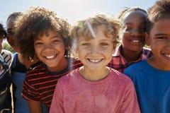 Fermez-vous des amis de la préadolescence en parc souriant à l'appareil-photo Images stock