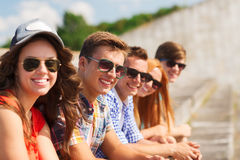 Fermez-vous des amis de sourire s'asseyant sur la rue de ville Photographie stock