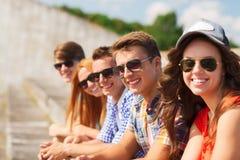 Fermez-vous des amis de sourire s'asseyant sur la rue de ville Photo libre de droits